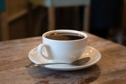 A mug of hot black coffee stands on a wooden table. White mug with coffee