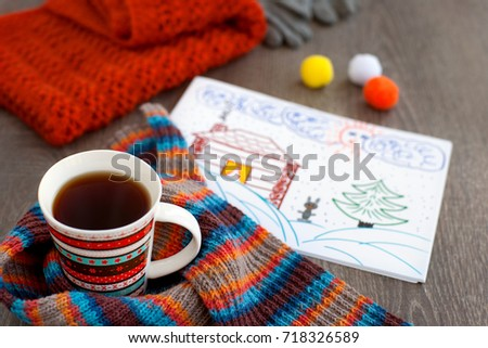 A mug of tea and a picture about winter. A cup of tea, a knitted scarf and a picture of snow, a Christmas tree and a warm house remind us of the winter. Tea for warming in the cold season.