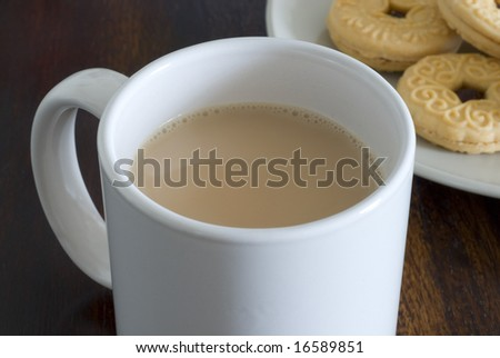 a mug of white tea and plate jam biscuits