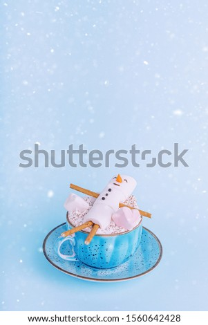 a mug with cocoa in which lies a happy marshmallow man. The concept of a warm Christmas and winter holidays warming drink #1560642428