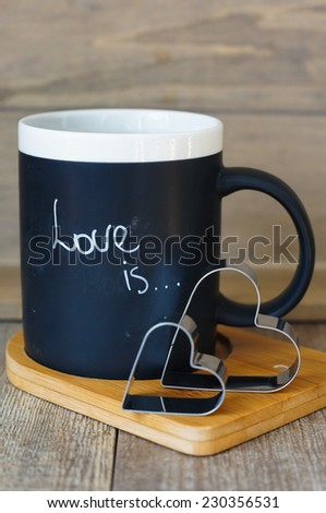 A mug with Love is note and valentine decoration on the wooden table