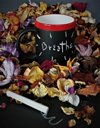 A mug with writable surface says Breathe, surrounded by dried blossoms, and a stick of chalk