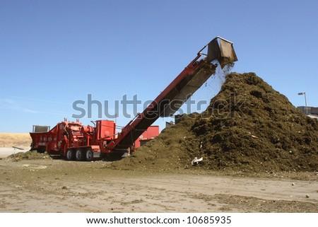 a mulching machine dumps into a pile of mulch