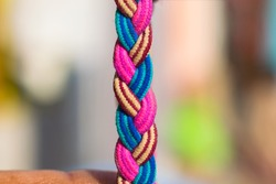 a multi color braided rope of pink,blue and dark brown color strings.a pattern of braided rope.