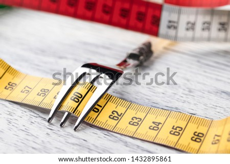 A multi-colored centimeter wrapped a dessert fork on an old wooden table showing the number 60. The concept of dietary nutrition to maintain a slim figure with parameters 36 24 36 or 90 60 90