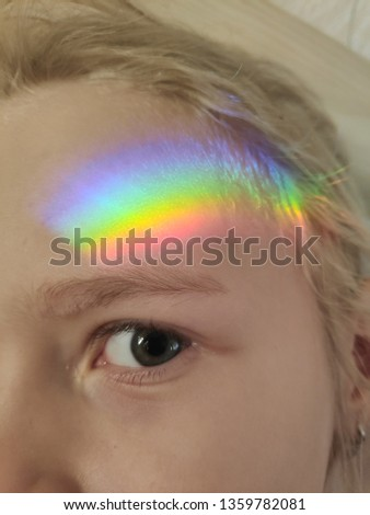 A multi-colored rainbow on a child's face. Photo close up. Amazing everyday. Children's view of the world. Children Protection Day. Color decomposition.