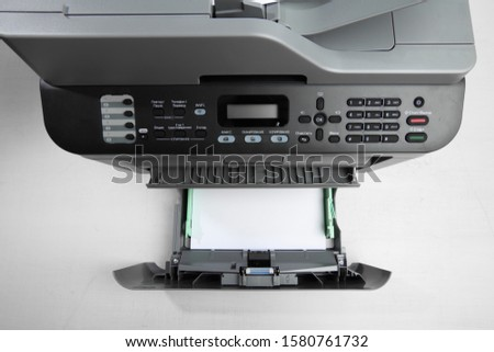 A multi function printer, copier, scanner on office table. top view. Reply, 2 pages, pause, 2in 1 passport , fax, options, wifi, copy, scan, print, stop, start #1580761732