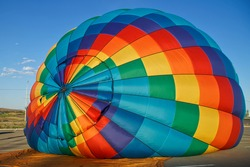 A multicolor hot air balloon is filled with hot air in a parking lot against a blue sky. Relaxation, variety and freedom. Abstraction and symbolism
