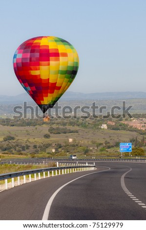 A multicoloured hot air balloon just about landing dangerously on a motorway.  Hills and a blue sky in the background.