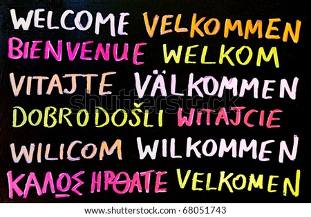 A multilingual welcome sign, written on a chalk board.