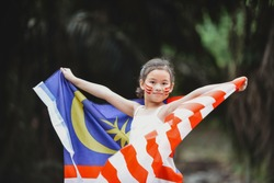 A multiracial Asian girl child holding and waving Malaysia flag. Patriotic students celebrating Independence Day. Children with facepaint. Happy and smiling on the road. Sabah Borneo.