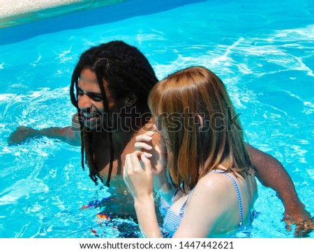 A multiracial couple in the pool enjoying the holidays - A redheaded girl and her black boyfriend playing in the pool #1447442621