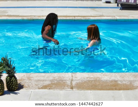 A multiracial couple in the pool enjoying the holidays - A redheaded girl and her black boyfriend playing in the pool #1447442627