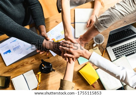 A multiracial team, colleagues put their hand on hand of one another. A sign of a close-knit multicaltural team, top view on the office desk Photo stock ©