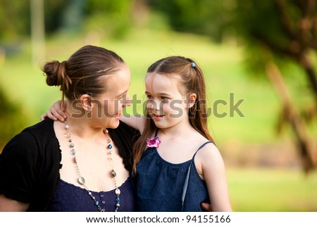 A mum with her 6 year old little girl in an outdoor field.  They are making eye contact