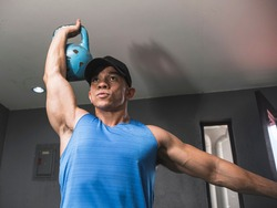 A muscular asian man does kettlebell overhead press. Upper body and shoulder workout at the gym.