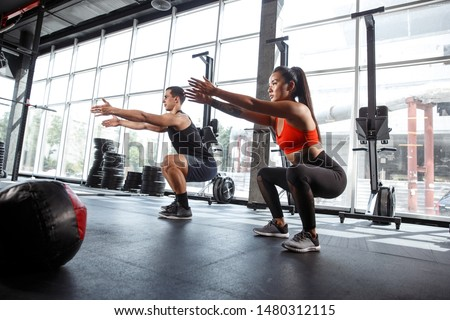 A muscular athletes doing workout at the gym. Gymnastics, training, fitness workout flexibility. Active and healthy lifestyle, youth, bodybuilding. Doing exercises together, training in squats.