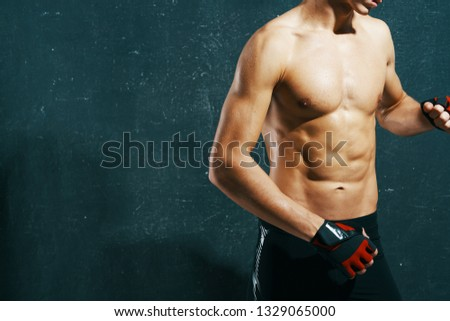 A muscular athletic man with a muscular muscular body in sport gloves Dark isolated background #1329065000