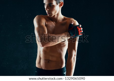 A muscular athletic man with a muscular muscular body in sport gloves Dark isolated background #1329065090