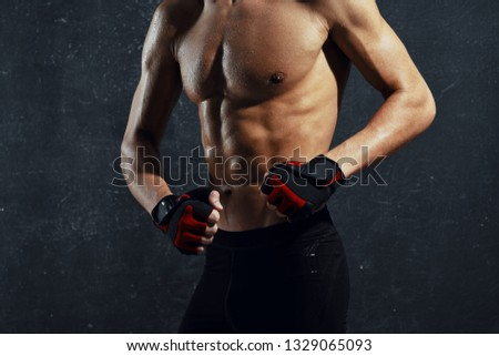 A muscular athletic man with a muscular muscular body in sport gloves Dark isolated background #1329065093