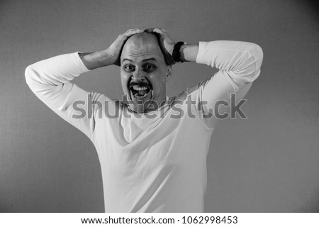 A muscular bald man with a mustache and a white jacket looks grimacing. Portrait. Black and white. #1062998453