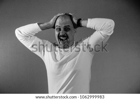 A muscular bald man with a mustache and a white jacket looks grimacing. Portrait. Black and white. #1062999983