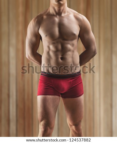 a muscular male torso on a background of the wooden wall - stock photo