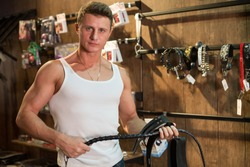 A muscular man in a vest holding a leather whip in the wooden room