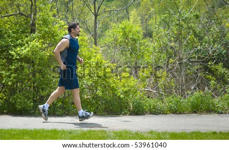 A muscular man jogging at the park.