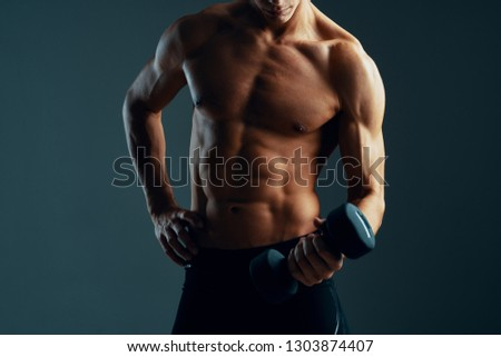 A muscular man with a muscular body and a muscular body pumped up is shaking dumbbell hands on a dark isolated background #1303874407