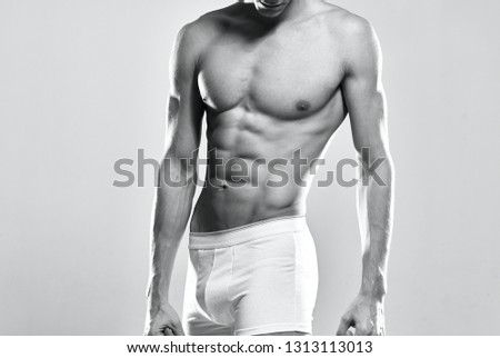 A muscular man with a muscular body in white shorts is a gray muscular isolated background sport fitness workout