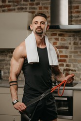 A muscular man with a white towel on the shoulders is posing with pull elastic rope in his apartment. The bodybuilder with tattoos on his forearms is demonstrating his sporty physique at home