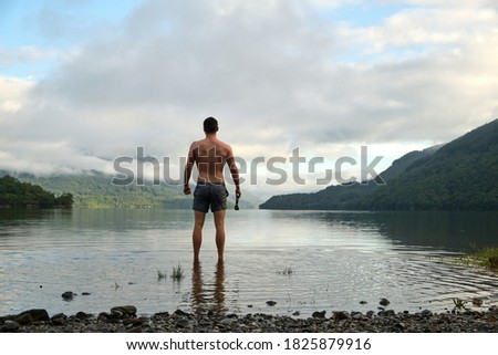 A muscular mid 20s male stands confidently after wild swimming in Loch Lomond, Scotland. Wearing swimming trunks and with swimming goggles in hand. Picturesque views all around. Relaxing wide shot.