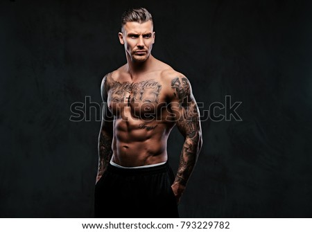 A muscular tattooed man on a dark background.