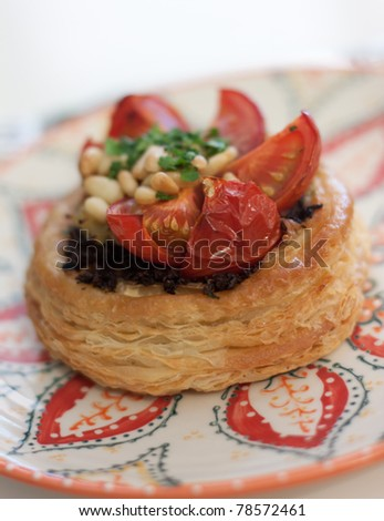 A mushroom and tomato tart sprinkled with pine nuts