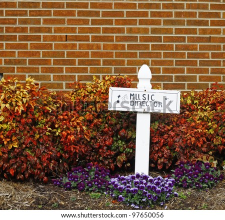 A music director cross among the spring flowers and foliage against a brick wall with room for your text.