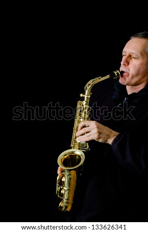 A Musician dressed in black is playing jazz music on his golden saxophone in front of a black background