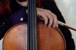 a musician with a bow and cello. rock cellist with colored hair