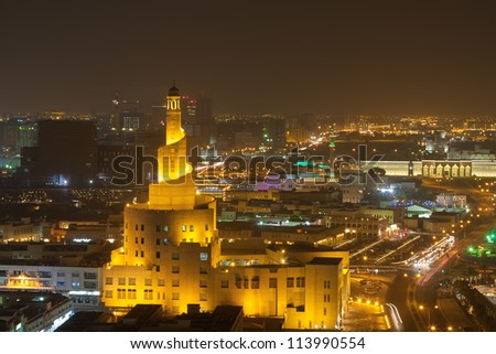 a muslim mosque lit up at night time showing the tower and city background