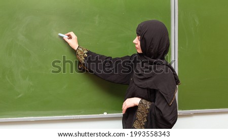 A Muslim teacher writes with chalk a blackboard.