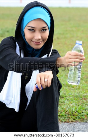 A Muslim woman athlete holding a bottle of mineral water