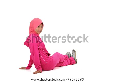 A muslim woman stretching her leg before jogging