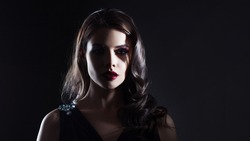 A mysterious gorgeous pale lady with dark hair and scarlet lipstick in the shade. Portrait in the noir style.
