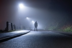 A mysterious man, alone, standing in the middle of a country road. Under street lights. On a foggy, moody, spooky, winters night