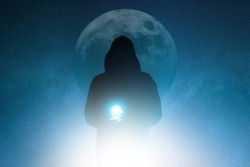 A mysterious moody hooded figure, holding a magical glowing light silhouetted against back light with the universe and stars behind him.