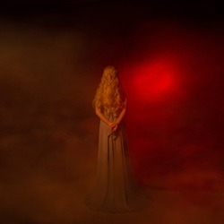 A mysterious woman blonde in a long gray dress goes to the gates of hell. The background is a fog that spreads along the ground and a red portal in the distance. Journey to the kingdom of Hades.