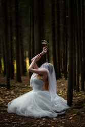 A mysterious woman bride with a veiled face in a gloomy forest in a prayer position with a bird crawling into her hand.