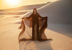 A mysterious woman in a black long dress stands in the desert. Luxurious clothes gold accessories hide the face. Oriental beauty fashion model. Sand dunes background orange sunset. hands raised to sky