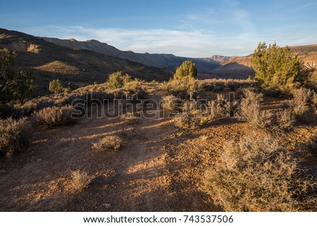A narrow ATV trail cuts through sage and juniper trees in Southern Utah just before sunset. in the distance the steep red cliffs of Kolob Canyon in Zion National Park stand above the horizon