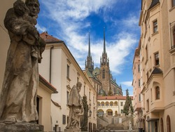 A narrow backstreet behind a huge Catholic cathedral with tall slender spires in a European city. A row of saints sculptures along the street. Blue sky with light clouds. No people